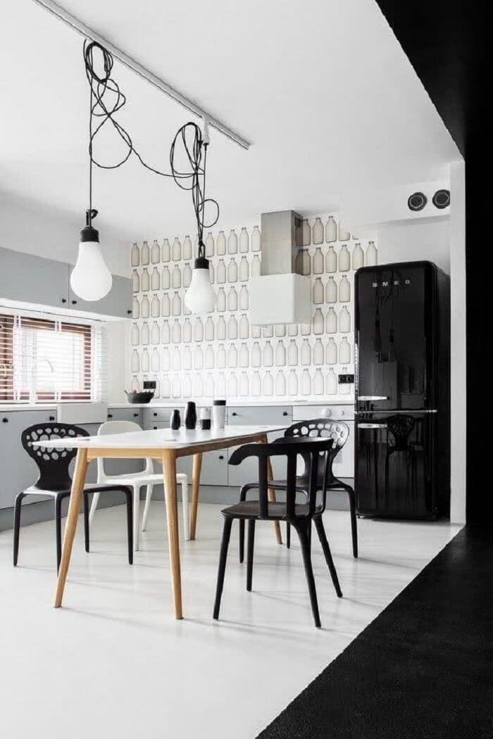 A geladeira preta se harmoniza com as cadeiras do ambiente