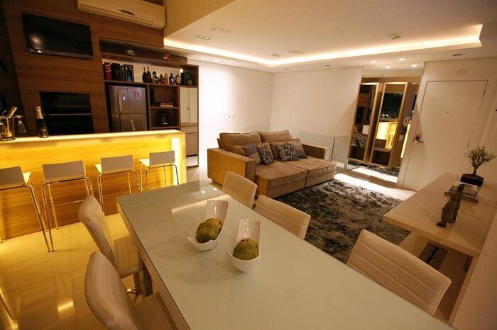 A mesa retangular branca da sala de jantar serve para dividir ambientes