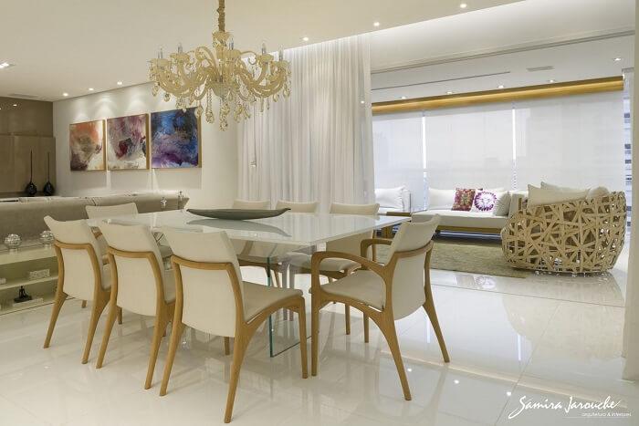 A mesa retangular da sala de jantar se integra ao ambiente da varanda