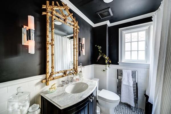 A moldura na cor dourado do espelho encanta a decoração do banheiro