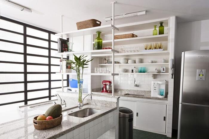 A pia da cozinha se faz presente em diferentes pontos do ambiente. Projeto de Antônio Ferreira Junior e Mário Celso Bernardes