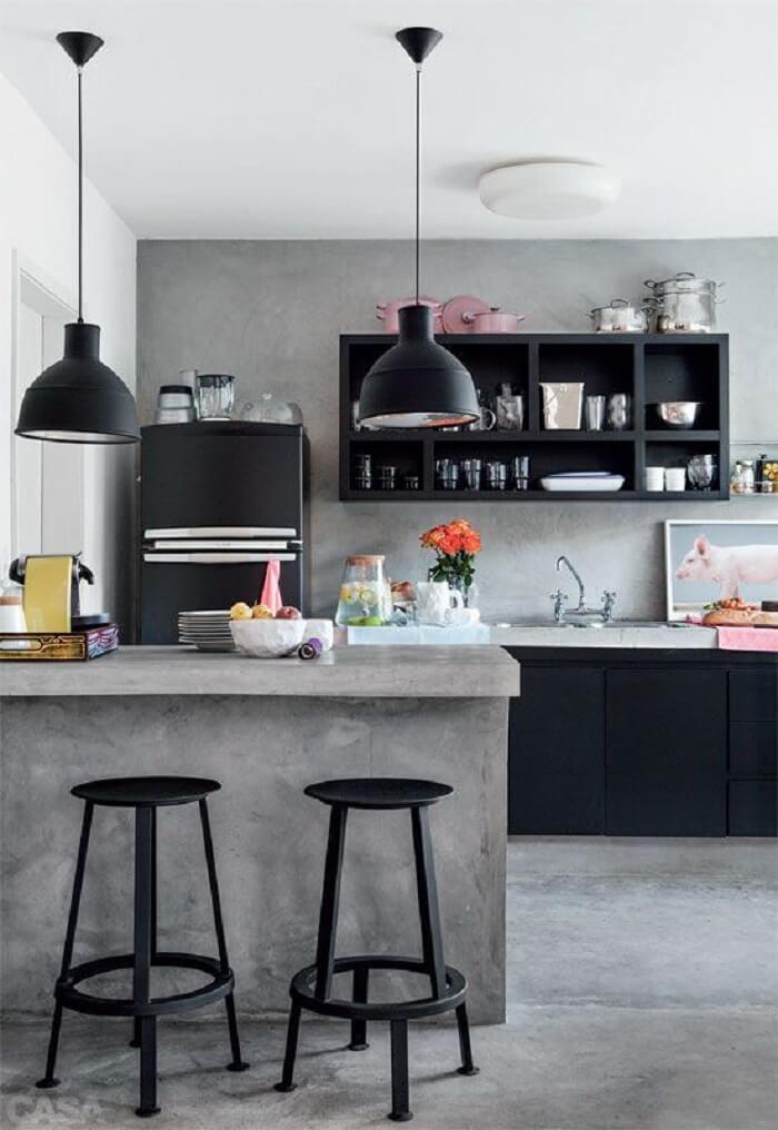 Cozinha americana com cimento queimado e geladeira preta duplex