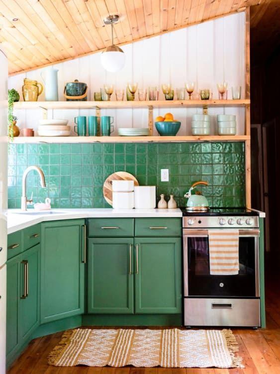 Cozinha com revestimento verde e armários