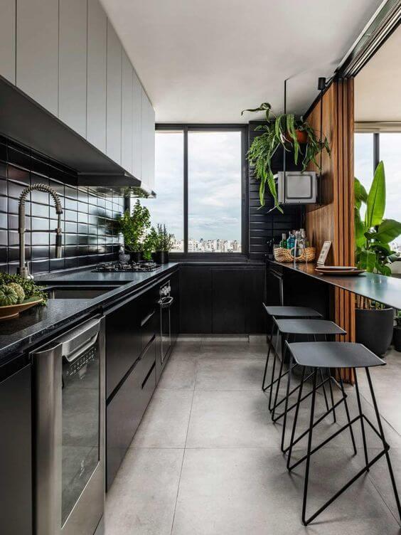 Cozinha moderna com piso de porcelanato cimento queimado e armários pretos