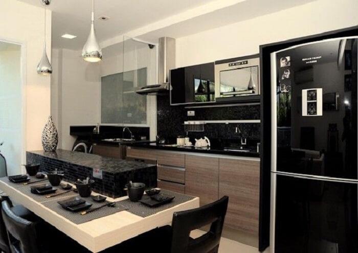 Cozinha planejada com bancada e geladeira preta embutida