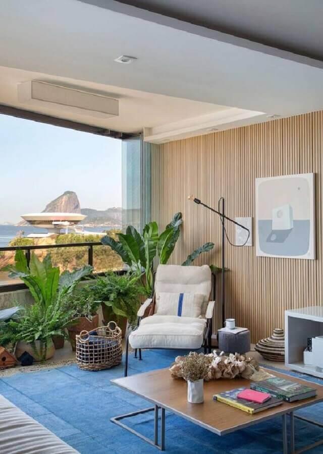 Decoração de varanda com tapete azul e parede amadeirada Foto Casa de Valentina