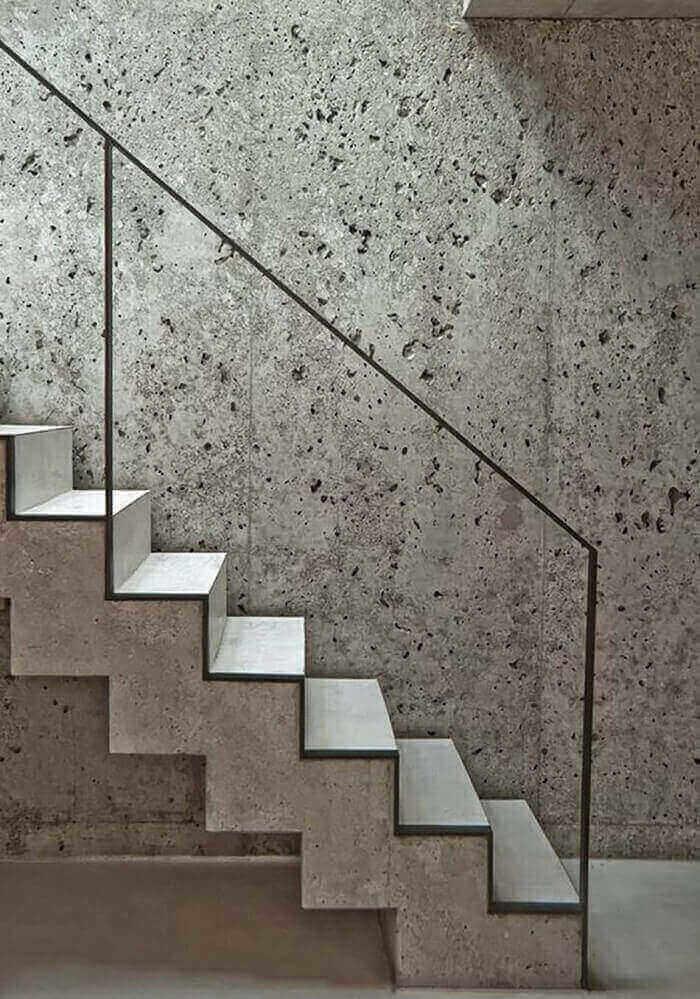 Escada flutuante de concreto com lateral feita de metal