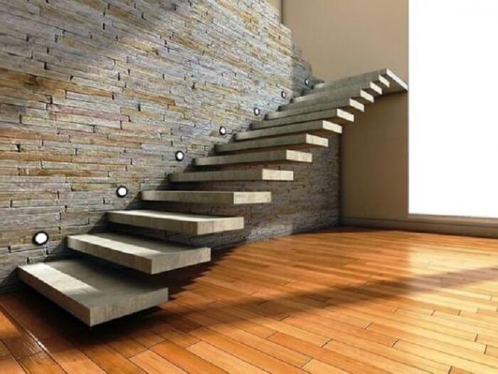 Escada flutuante de concreto com pontos de luz fixada em uma parede de pedra