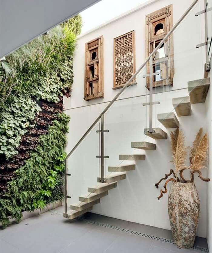 Escada flutuante de concreto e parede com jardim vertical