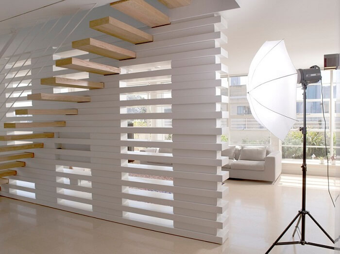 Escada flutuante de madeira clara se harmoniza com a parede branca