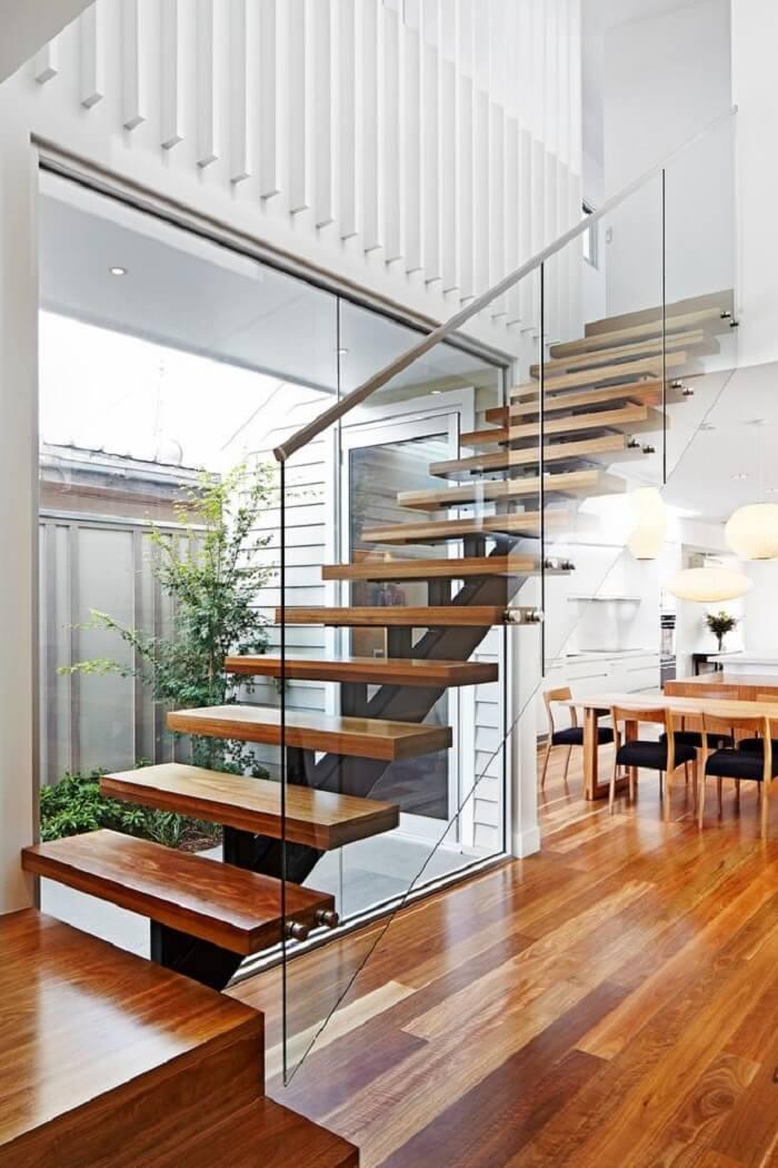 Escada flutuante de madeira com lateral de vidro