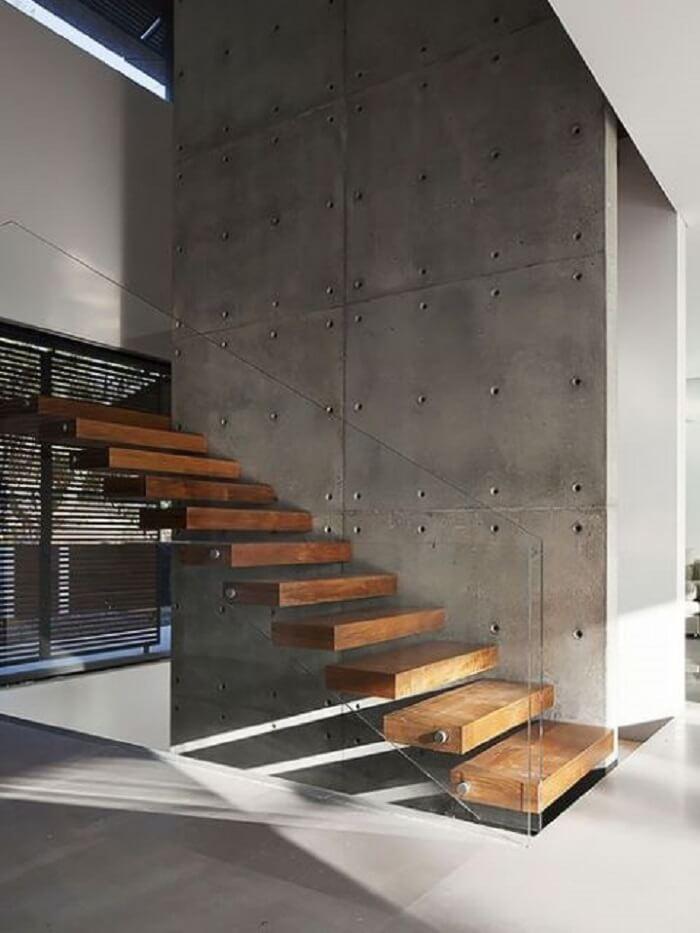 Escada flutuante de madeira fixada em parede de cimento