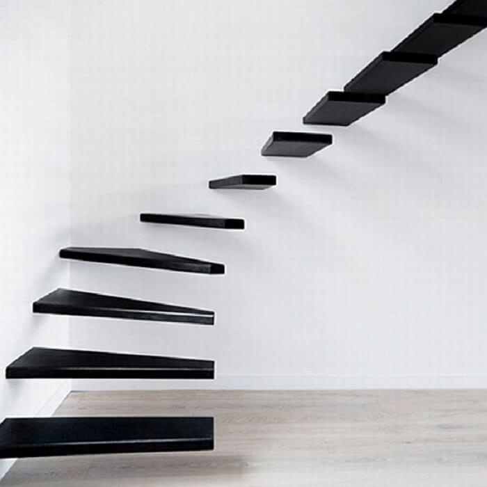 Escada flutuante de madeira preta fixada a uma parede branca