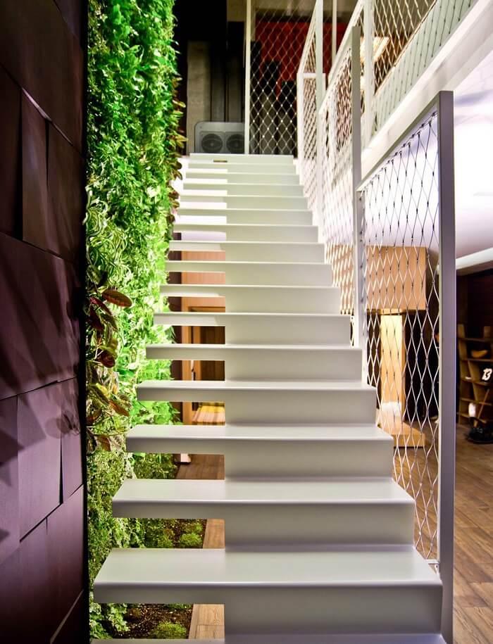 Escada flutuante super charmosa alinhada a uma parede com jardim vertical