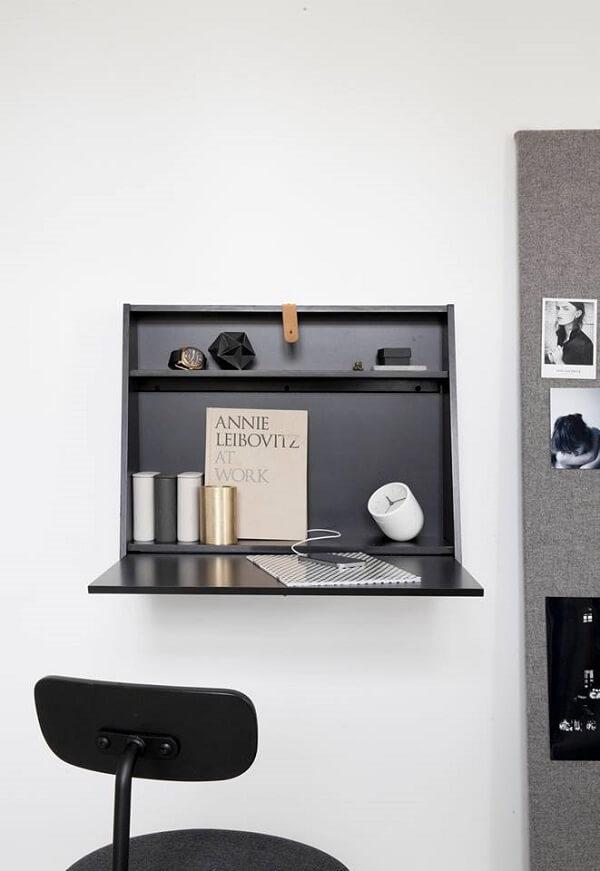 Escrivaninha preta dobrável de parede maximiza o espaço do ambiente