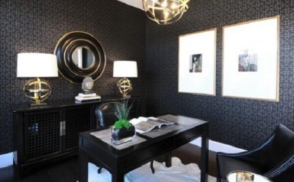 Escrivaninha preta e o espelho redondo com detalhes em dourado complementam a decoração do ambiente