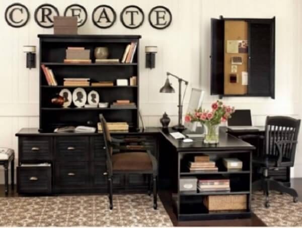 Escrivaninha preta em formato L com nichos embutidos maximiza a decoração do ambiente