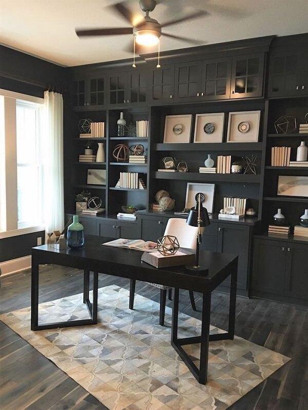 Escrivaninha preta posicionada dentro do home office