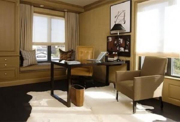 Home office com decoração bege e dark com escrivaninha preta e obras de arte