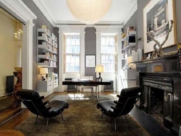 Home office com decoração elegante dispõe da presença de uma escrivaninha preta