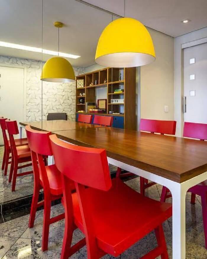 Mesa retangular com tampo de madeira e cadeiras na cor vermelha