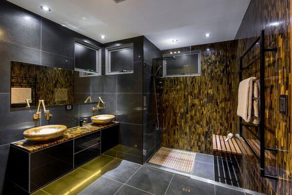 O dourado presente no revestimento da parede e no armário do banheiro encanta a decoração
