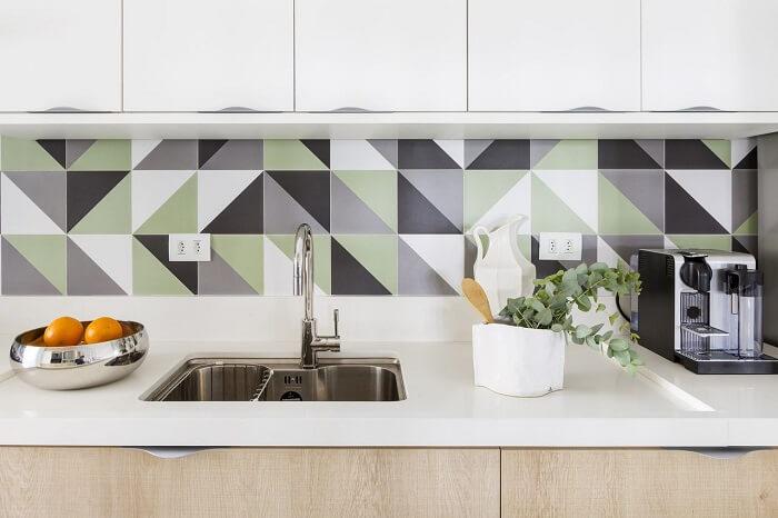 O revestimento geométrico traz um toque diferenciado para a pia de cozinha. Projeto de Bárbara Dundes