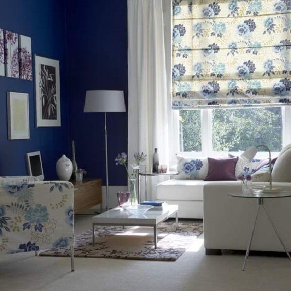 O tecido da persiana romana está presente nas estampas da poltrona e almofadas do ambiente