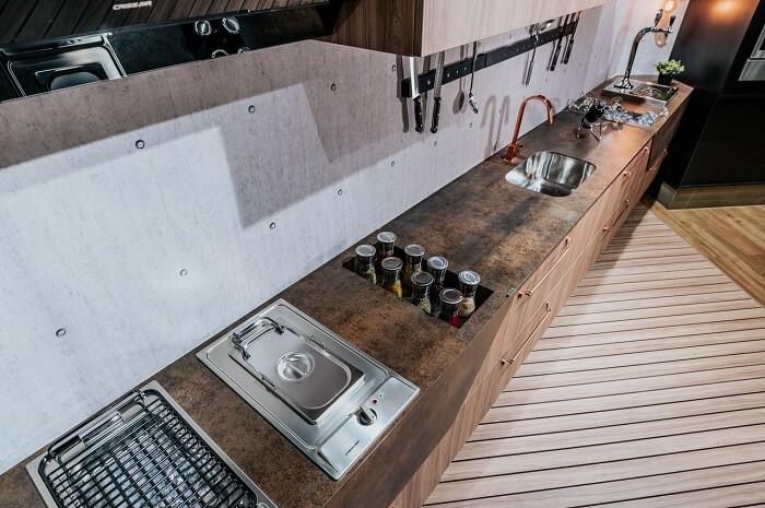 Parede com placas cimentícia e pia de cozinha planejada com acabamento diferenciado. Projeto de Nanoprice Marmoraria Online