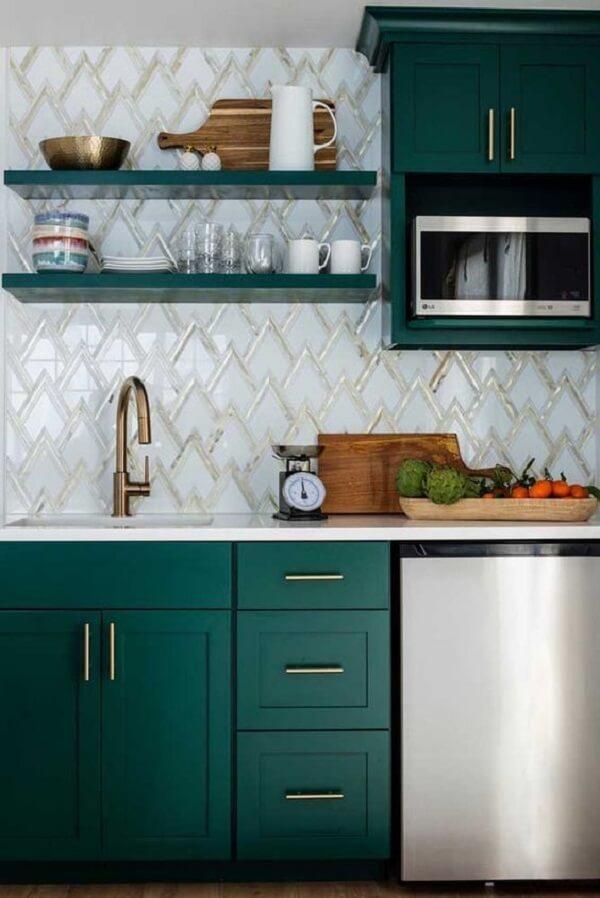 Pia de cozinha com torneira dourada e armários planejados em marcenaria verde. Fonte: Revista Viva Decora