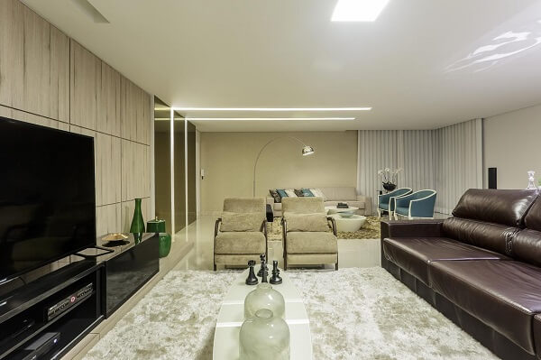 Sala de estar com recorte no teto feito com moldura de gesso