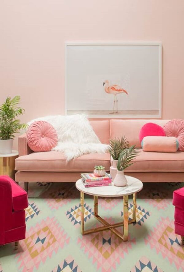 Sala de estar com sofá retrô na cor rosa e mesa de centro com pés em dourado