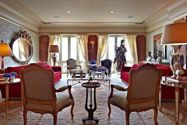 Sala de estar com sofá vermelho e poltronas com acabamento em dourado