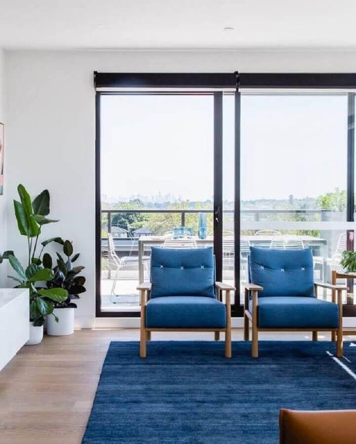 Sala de estar decorada com poltronas e tapete azul Foto Histórias de Casa