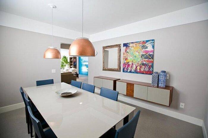Sala de jantar com mesa retangular branca e cadeiras na cor azul