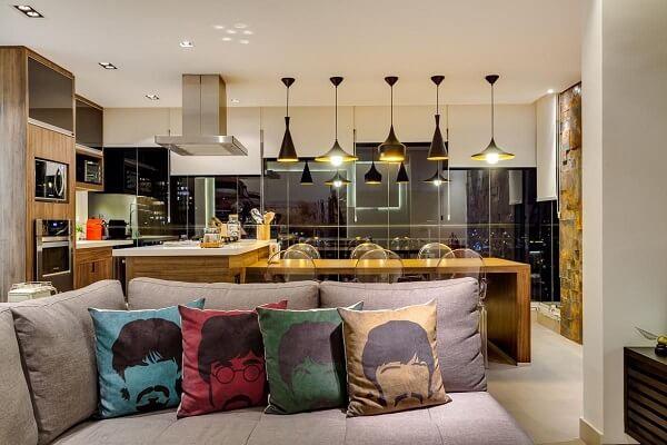 Sala de jantar com sala de estar integrada apresenta elementos em dourado