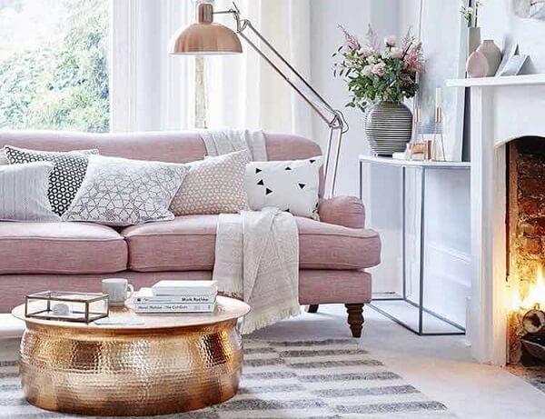 Sofá rosa e mesa de centro dourado encanta a decoração desta sala de estar
