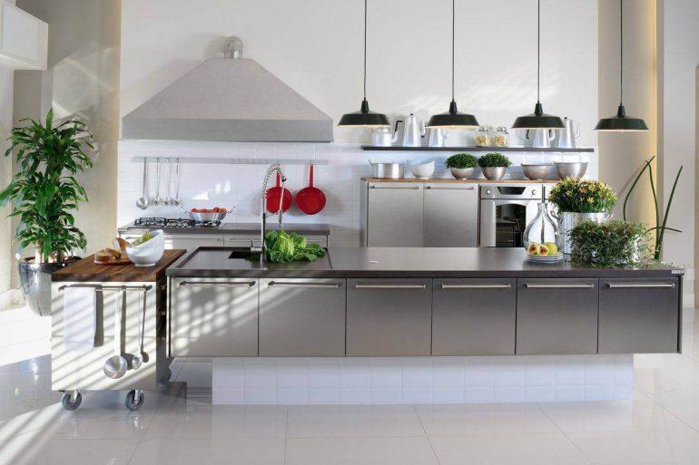 Decoração de cozinha moderna com pendentes pretos e armários em aço inox