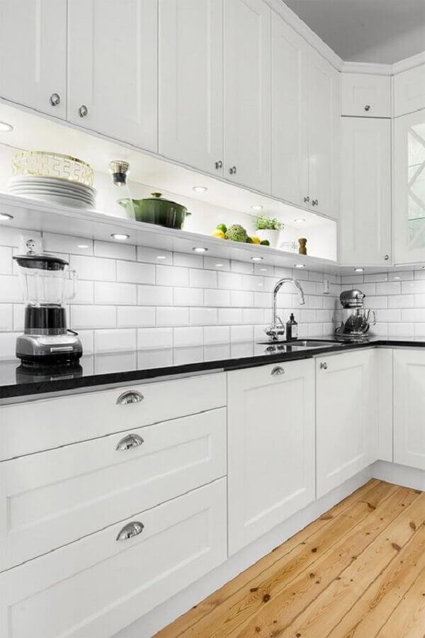 cozinha branca decorada com piso de madeira e bancada preta com iluminação embutida Foto Ape L208