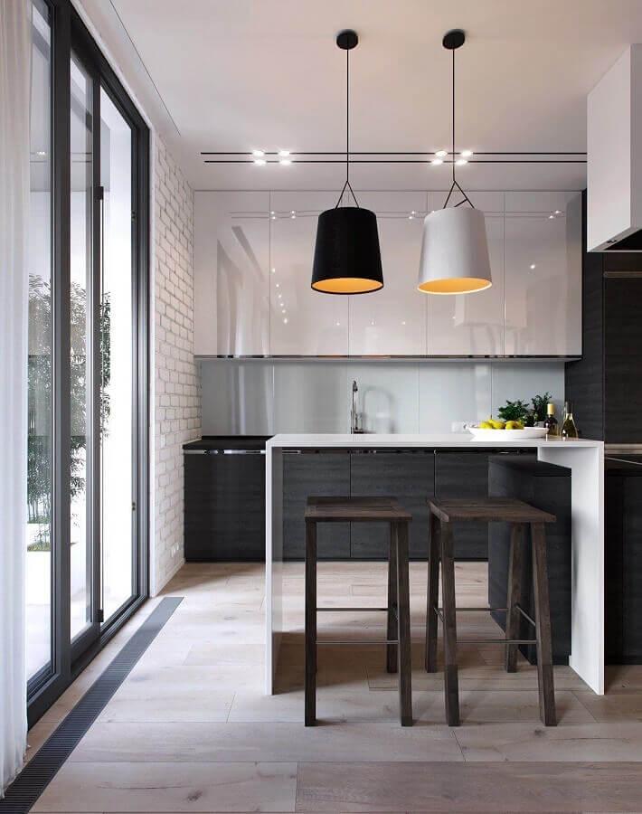 cozinha preta e branca decorada com banquetas de madeira e luminárias pendentes Foto ACC Guinee