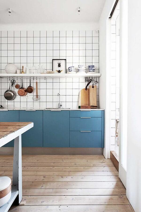 cozinha simples decorada com armário planejado azul petróleo e piso de madeira Foto Apartment Therapy