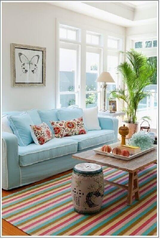 decoração clean para sala com sofá azul claro e tapete colorido listrado Foto Pinterest