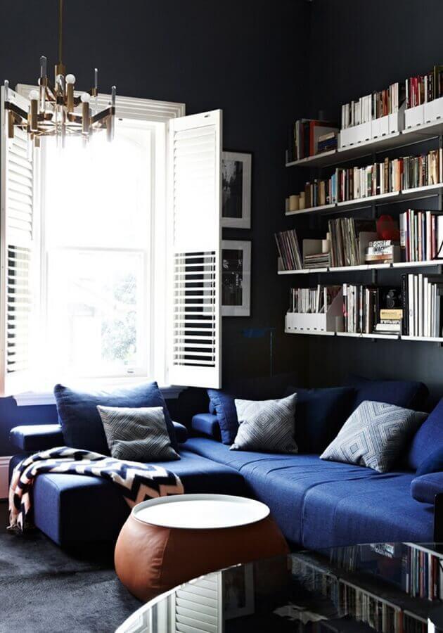 decoração com sofá azul escuro e prateleiras para livros Foto Yandex