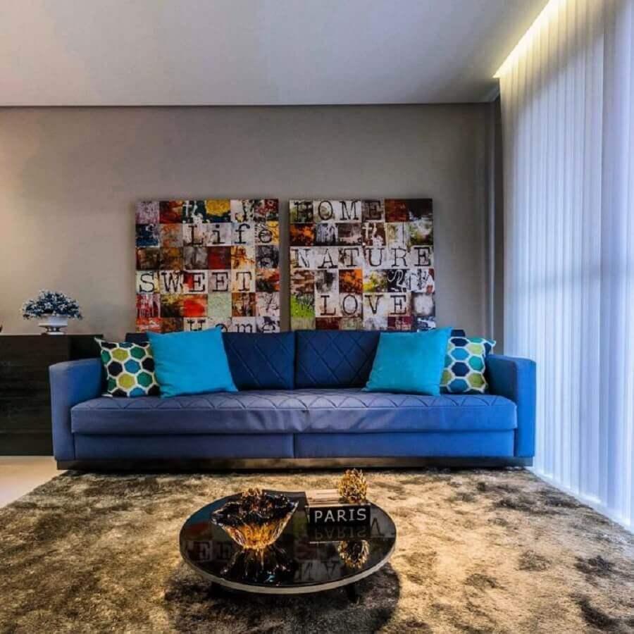 decoração para sala com sofá azul e quadros coloridos Foto Lo Interiores