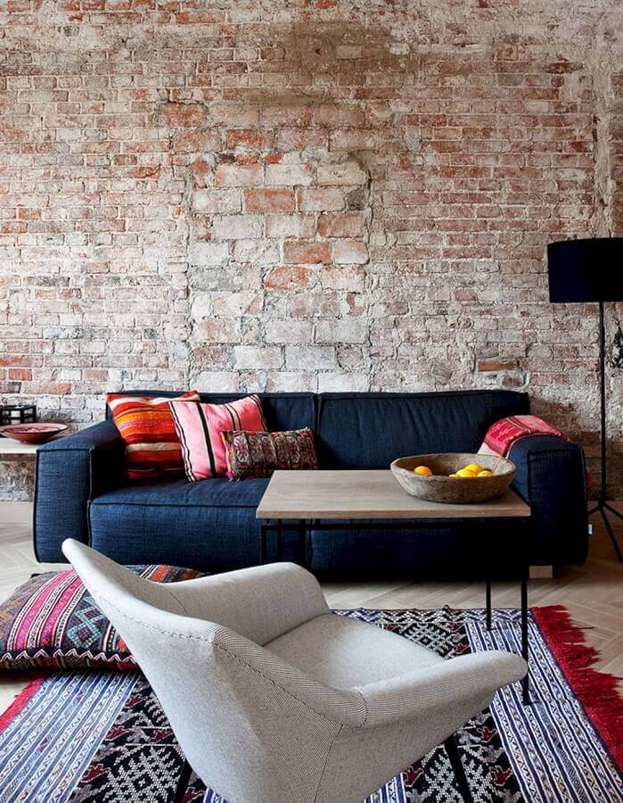 decoração rústica para sala com parede de tijolinho e sofá azul escuro Foto yandex