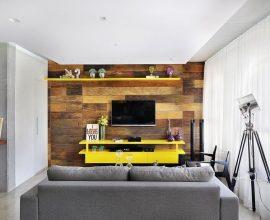 decoração sala de estar com rack amarelo e parede com revestimento de madeira