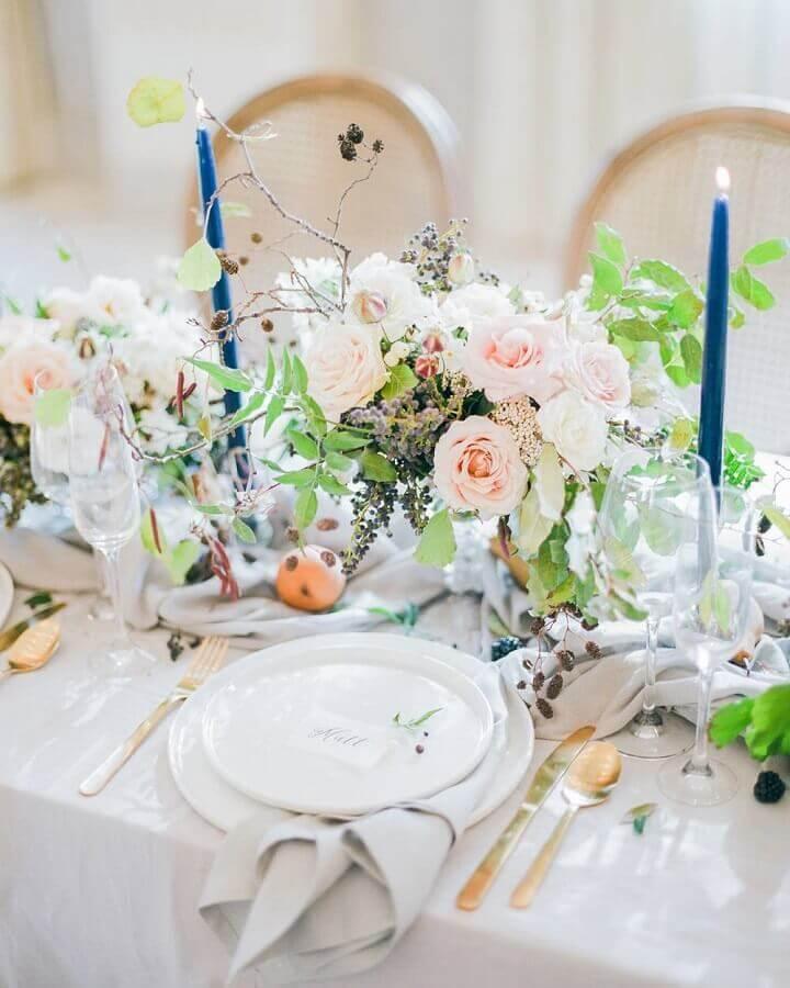 enfeite de mesa para casamento com arranjo de flores e velas azuis Foto Assetproject
