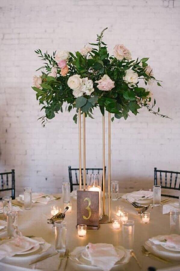 enfeite de mesa para casamento com arranjo de flores sobre suporte dourado Foto Pinterest