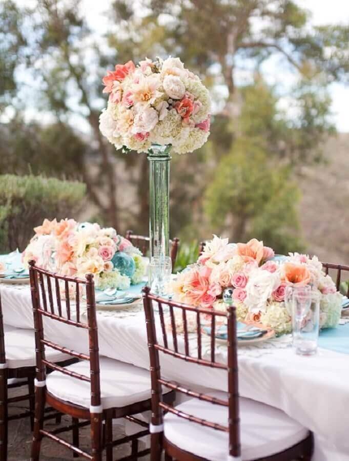 enfeites de casamento para mesa de convidados ao ar livre com grandes arranjos de rosas Foto Portal das Noivas