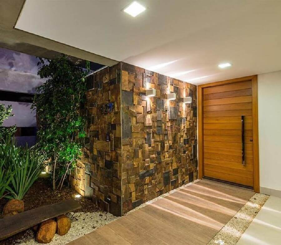 entrada com porta de madeira e pedra ferro Foto URBEM Arquitetura Ltda